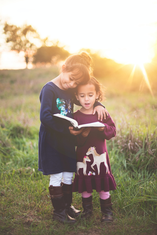 Duas meninas, que aparentam ter entre dois e cinco anos, em pé, abraçados, lendo um livro. Elas estão na natureza, em um gramado, com o pôr do sol ao fundo.