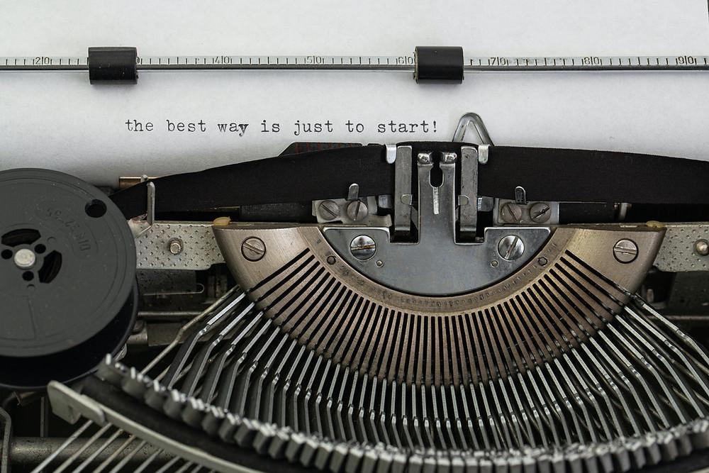 Parte de uma máquina de escrever, com foco na área em que as letras atingem o papel. Na folha, apenas uma frase: the best way is just to start!