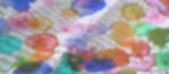 beschriebenes und gefaltetes Papier, das Farbspritzern in rot gelb und blau abbekommen hat