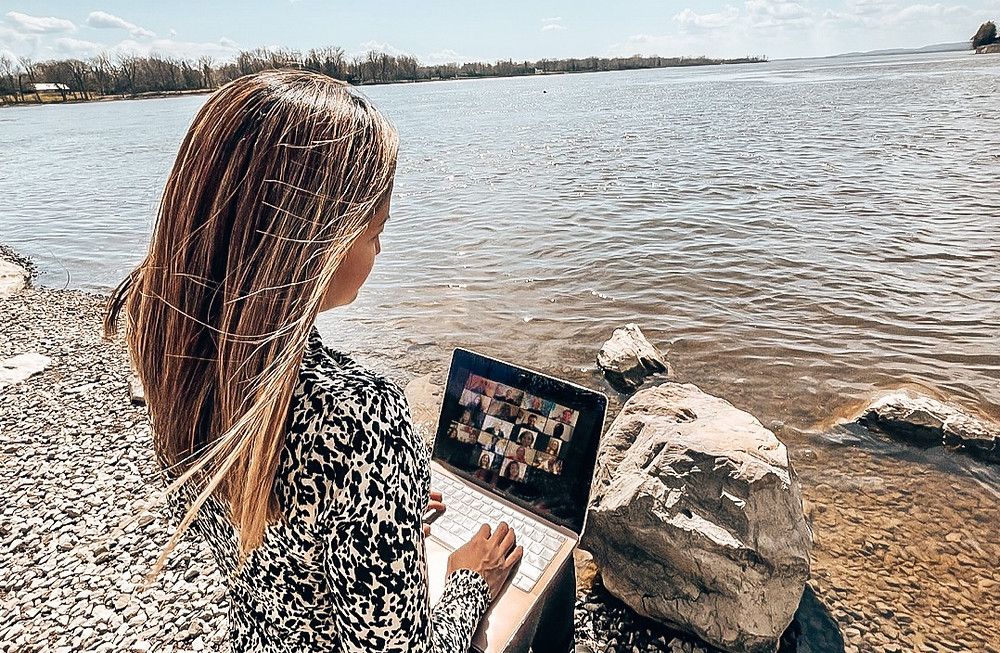women working on laptop with lake view