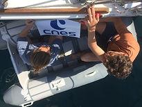 L'équipe SEA Plastics 2019 collant les logos des partenaires scientifiques et financiers sur la coque du voilier