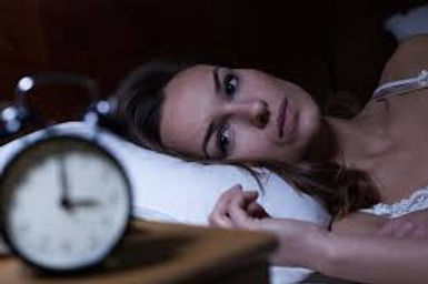 A middle aged women is laying in bed with eyes open and a distrubed look on her face. In the foreground is a clock showing 3am. She is suffering from insomnia.