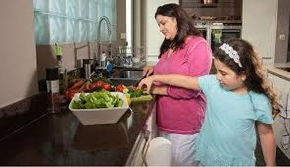 A photo of a mother and daughter in their kitchen preparing a salad together. This is to illustrate good nutrition haibts necessary for weight loss.