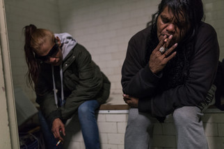 """Joy, an aboriginal lady, (right) smokes a cigarette with a friend in a shared bathroom. She has recently arrived at the Gatwick, but already considers the place as """"her second home"""". May 2017."""