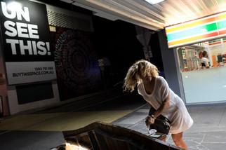 Charleze attend devant le 7-Eleven en face du Gatwick. A gauche, un panneau proposant de visiter des biens mis à la vente. La pression immobilière est très forte à Saint-Kilda. Certains restaurants et magasins souhaitent la fermeture du Gatwick.  Mai 2017.