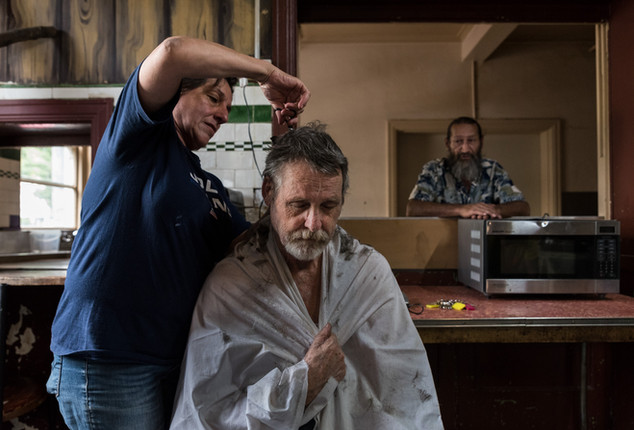 """Yvette cuts residents' hair for free. The night watchman, 55-year-old Mickael, was 17 when he first arrived at the Gatwick. He returned there 6 years after his divorce. His best memory about the Gatwick? """"People. All have a good side, you just have to find it. Sometimes you have to dig a long time (laughs)."""" February 2017."""