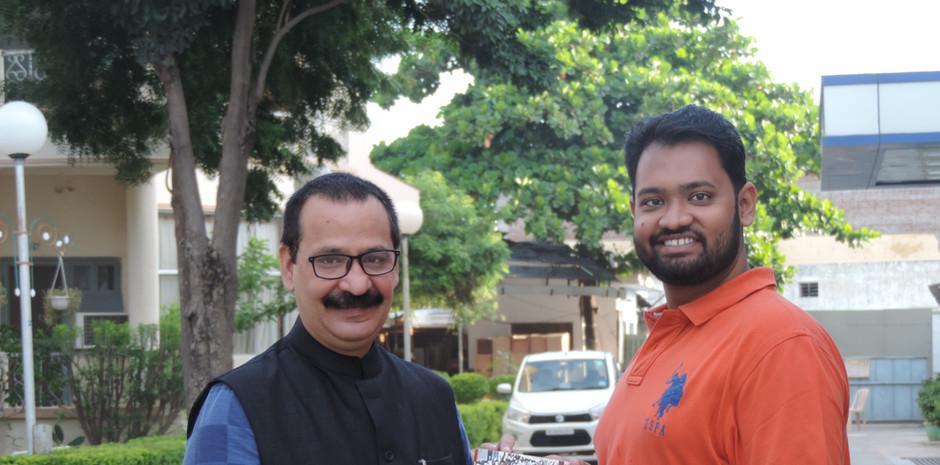 Prof. Sanjay Dwivedi, Head - Mass Communication at Makhanlal Chaturvedi - National University of Journalism and Communication gifting his book to Mr. Daksh Gaur, Founder, Blub World.