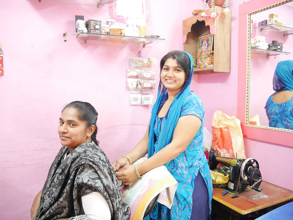 A smiling woman in a bright pink beauty parlour