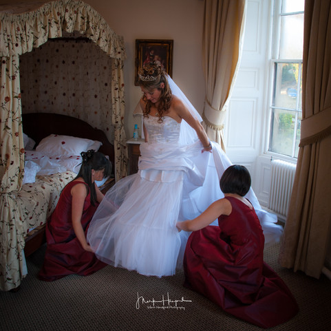 Bride getting some assistance from bridesmaids