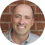 Image of Mike smiling who has a bald shaven head and standing in front of a brick wall.