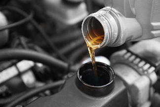 Pouring oil to car engine, close up.jpg