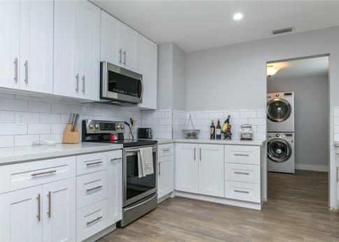 Contemporary All-White Kitchen Remodel Featuring Custom Cabinetry, Quartz & Subway Backsplash Tiles