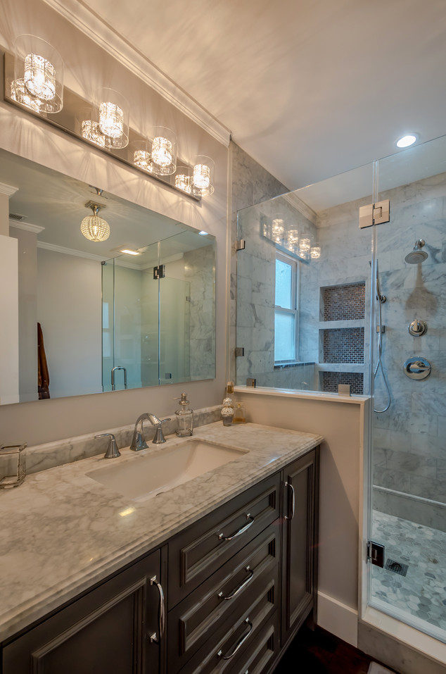 Bathroom Remodel Highlighted By Marble Tile Shower, Custom Shower Niches, Gray Wood Vanity, Marble Countertop & an Elegant Mirror/LED Vanity Lighting Set