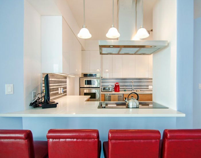 Modern Kitchen Design Highlighted by Pendant Lighting, Range Hood & a Pop of Red from Kitchen Bar Stools