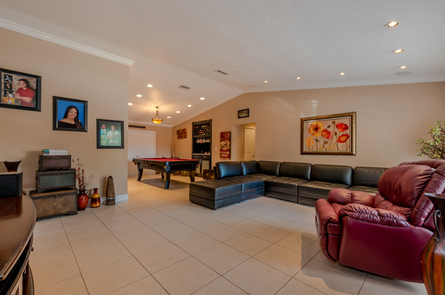 Open-Layout Living Room Featuring Vaulted Ceilings & Recessed LED Lighting That Blends Into Game Room
