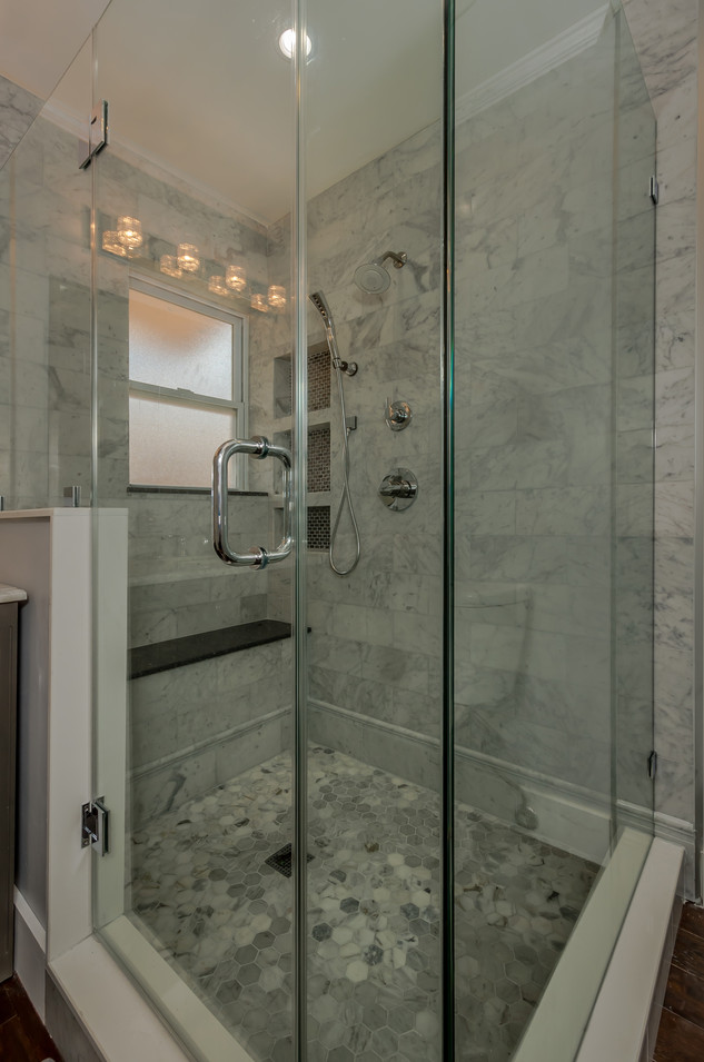 Custom-built Marble Tile Shower with a Shower Bench, Multiple Shower Niches & Shower Heads and Frameless Shower Glass Doors