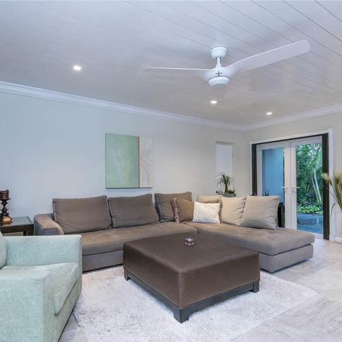 Spacious Living Room Design Featuring Wood Plank Ceiling & Recessed Lighting