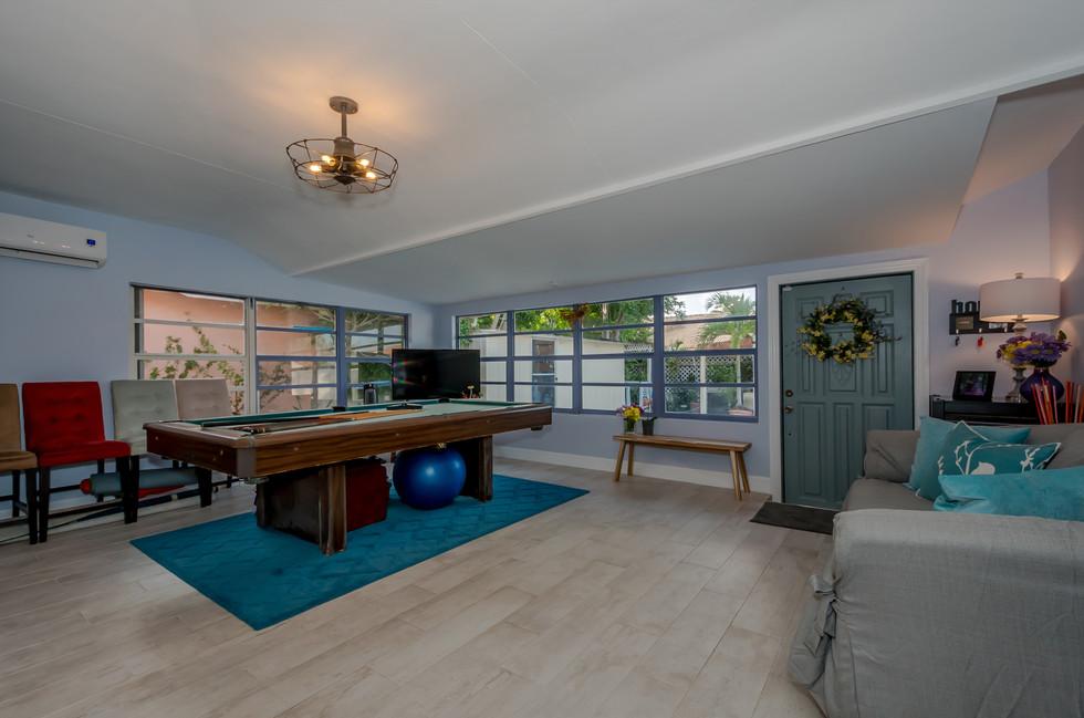 Stylish Game Room Featuring Wood Plank Tiles & Elegant Lighting