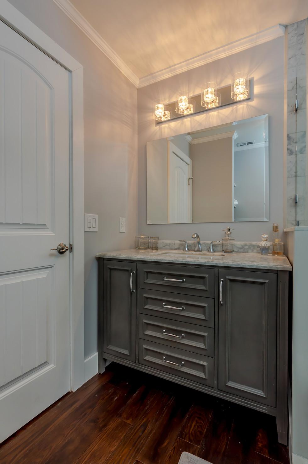 Bathroom Remodel Highlighted By a Gray Wood Vanity with Marble Countertop, Elegant Vanity Mirror & Bright LED Vanity Lighting