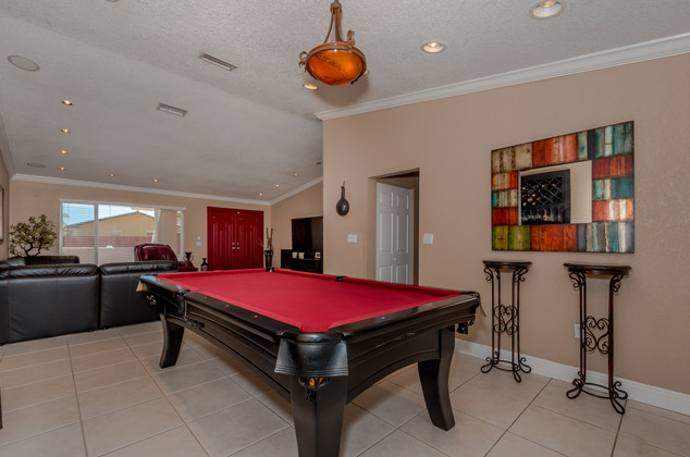 Game Room Featuring Vaulted Ceilings, Recessed LED Lighting & an Open Layout Transition Towards Living Room
