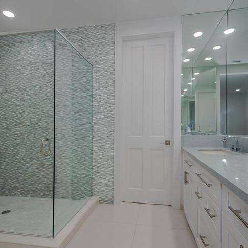 Elegant Jack & Jill Bathroom Remodel Featuring Accent Wall of Marble Mosiac Tile & Matching Quartz