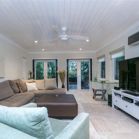 Spacious Living Room Design Featuring Wood Plank Ceiling & Recessed Lighting 3