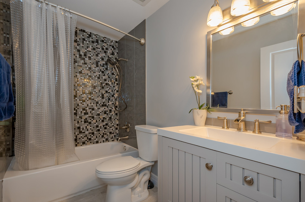 Contemporary Guest Bathroom Remodel Featuring Light Gray Vanity & Beautiful Shower Tiles