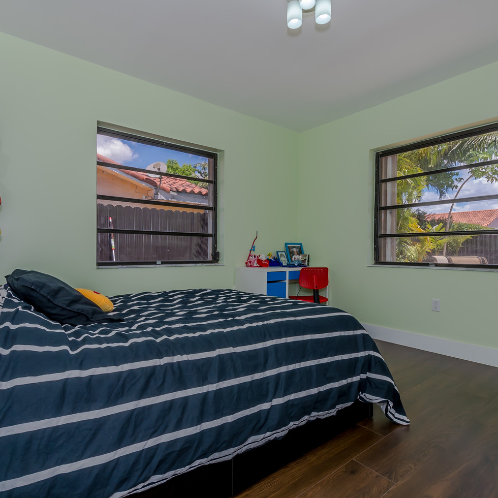 Newly-Remodeled Guest Bedroom Featuring Wood Flooring & Bright Paint Color