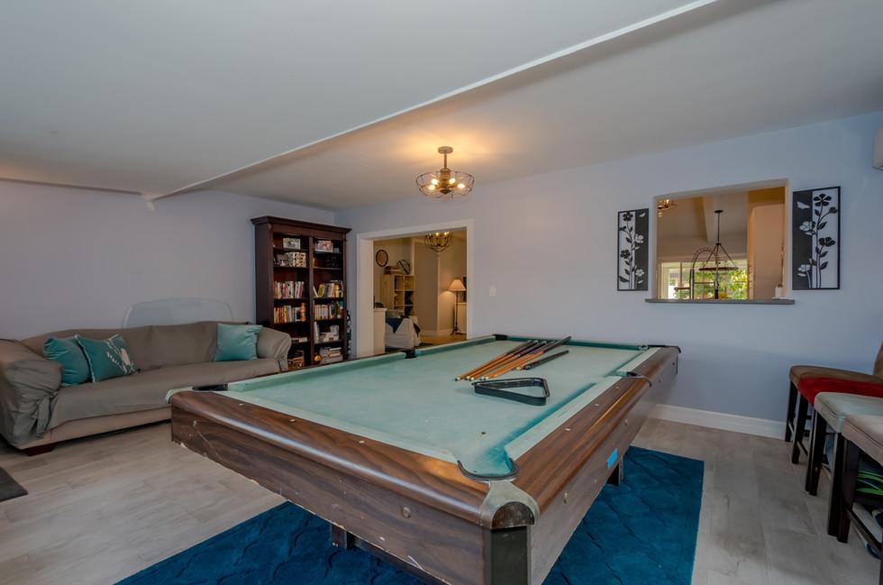 Stylish Game Room Featuring Wood Plank Tiles & Elegant Lighting 2