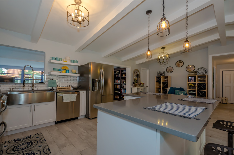 Breathtaking Southwestern Interior Design Remodel Featuring Custom-Built White Kitchen Cabinets Contrasted by Gray Quartz, Subway Tiles & Decorative Wood Trusses