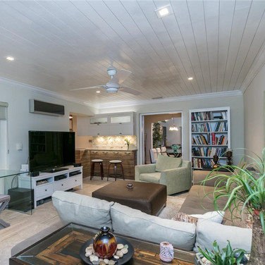 Spacious Living Room Design Featuring Wood Plank Ceiling & Recessed Lighting 2
