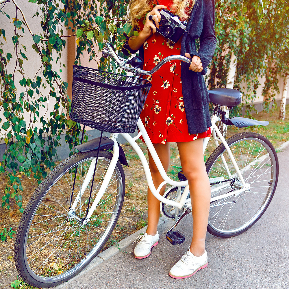 A lady with a bike holding a camera in one hand