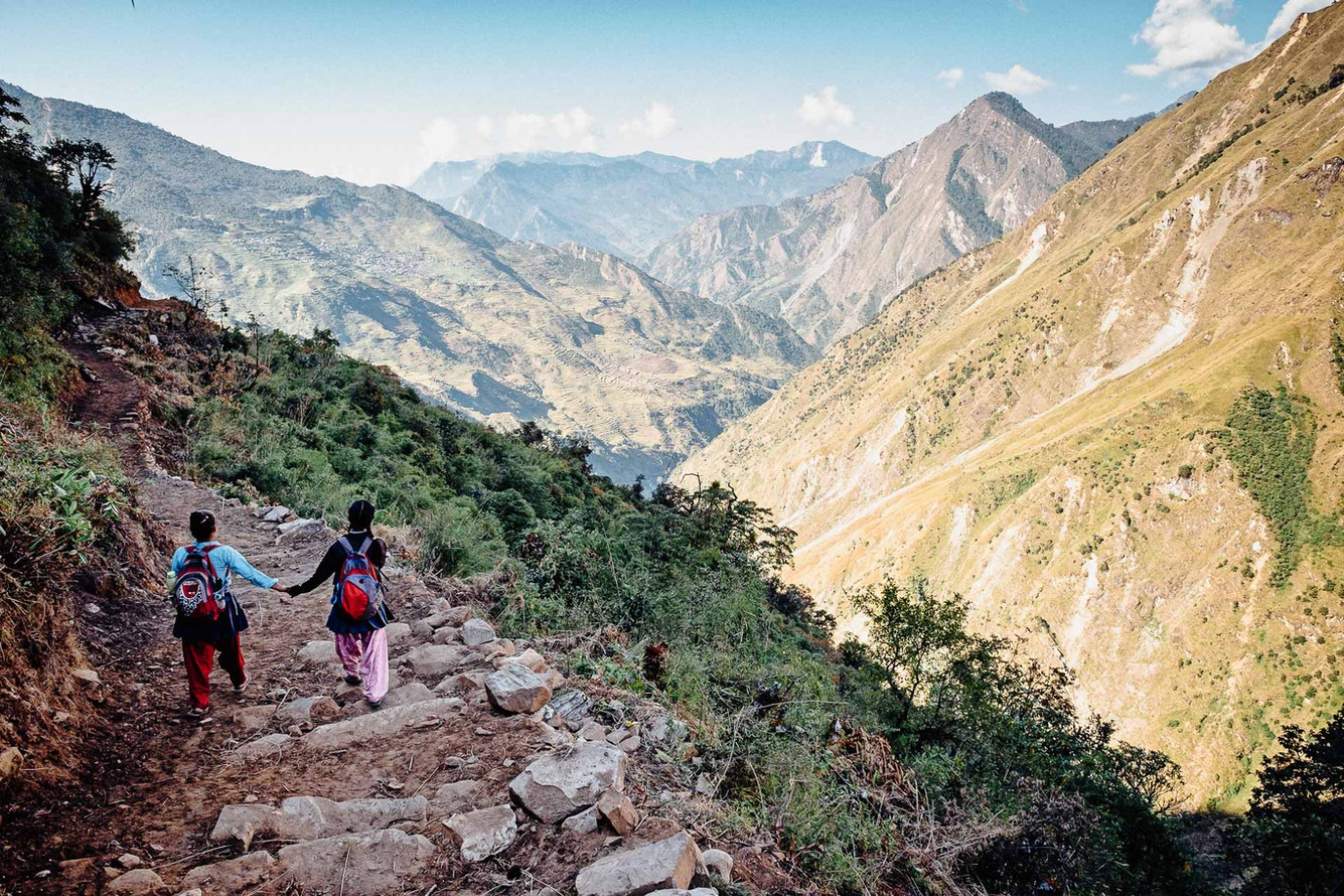 Ambrita Ghale and her close friend walk the 1,5 hour path to school (in the background). During the monsoon season, the path from Lingjo to Laptung becomes very slippery.