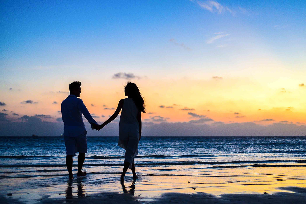 Couple holding hands by the sea at sunset