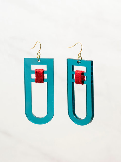 The Torii Drop Earrings by Sunny Side Studio in transparent teal with red thread
