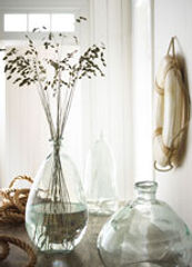 Product Photography of two clear glass vases in bright white seaside room.