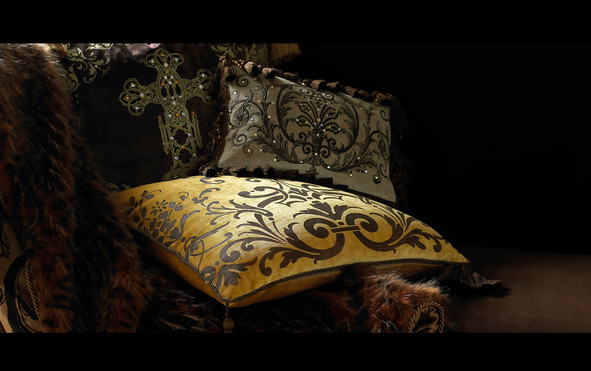 Bedding Photography: Moody lighting on embellished pillows grouped on dark sofa.