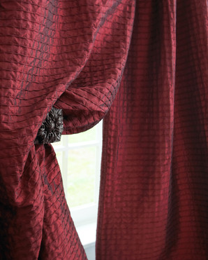 Window Photography: Close-up view of burgundy stitched drapery with tie-back for Horchow.