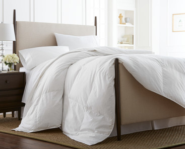 Bedding photography: Queen linen bed with white duvet gracefully draped across footboard for Downlite.
