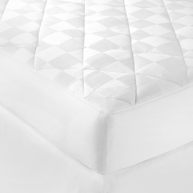 Bedding Photography: Corner view of white checkered mattress pad on bed with white dust skirt.