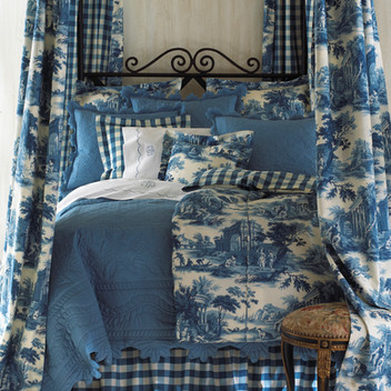 Bedding Photography: Foot view photography of blue toile bedding with matching blue toile bed drapes at each corner.