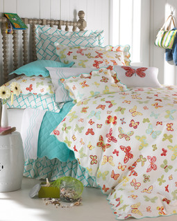 Bedding Photography: Colorful butterfly patten bedding paired with aqua coverlet for Neiman Marcus photographed in white plank wall room.