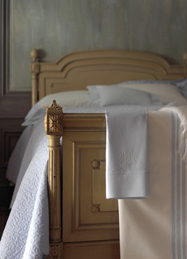 Bedding Photography: Blue and white mongrammed sheets draped over footboard.