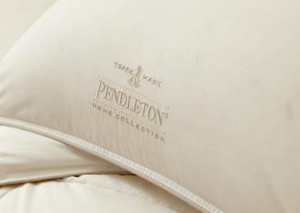Bedding Photography Close-up photo of Pendleton logo on cream pillowcase.