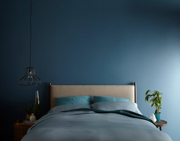 Bedding Photography: Foot view for Behr 2019 Trends Project of Blue Duvet on bed.  Wall painted the color Blueprint.