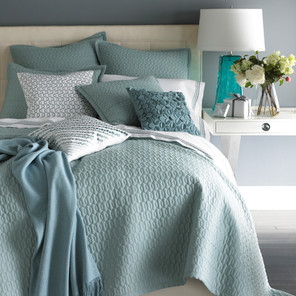 Bedding Photography: Foot view of bed with green coverlet and eight pillows against gray wall photographed for Neiman Marcus.