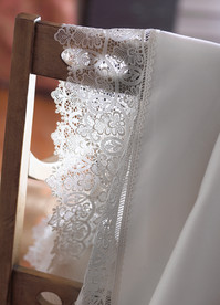 Bedding Photography: Close-up view of fancy white lace border sheets draped over a wood chair back.