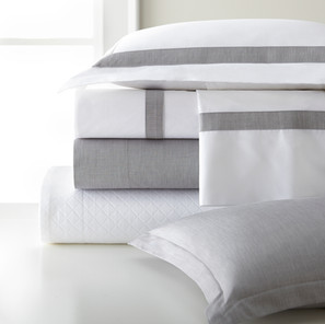 Bedding Photography: Legacy Home brand gray stripe bedding shown in a stack with two pillows on white surface in front of window.