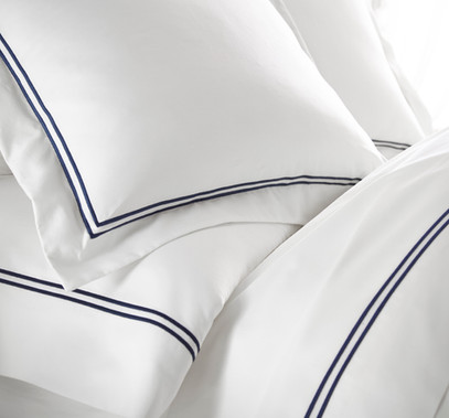 Bedding Photography: close-up of white bedding with double navy stripe border.
