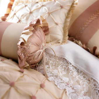 Bedding Photography: Close-up view of pink neckroll pillow and tow other pillows against lace sheet for Horchow.